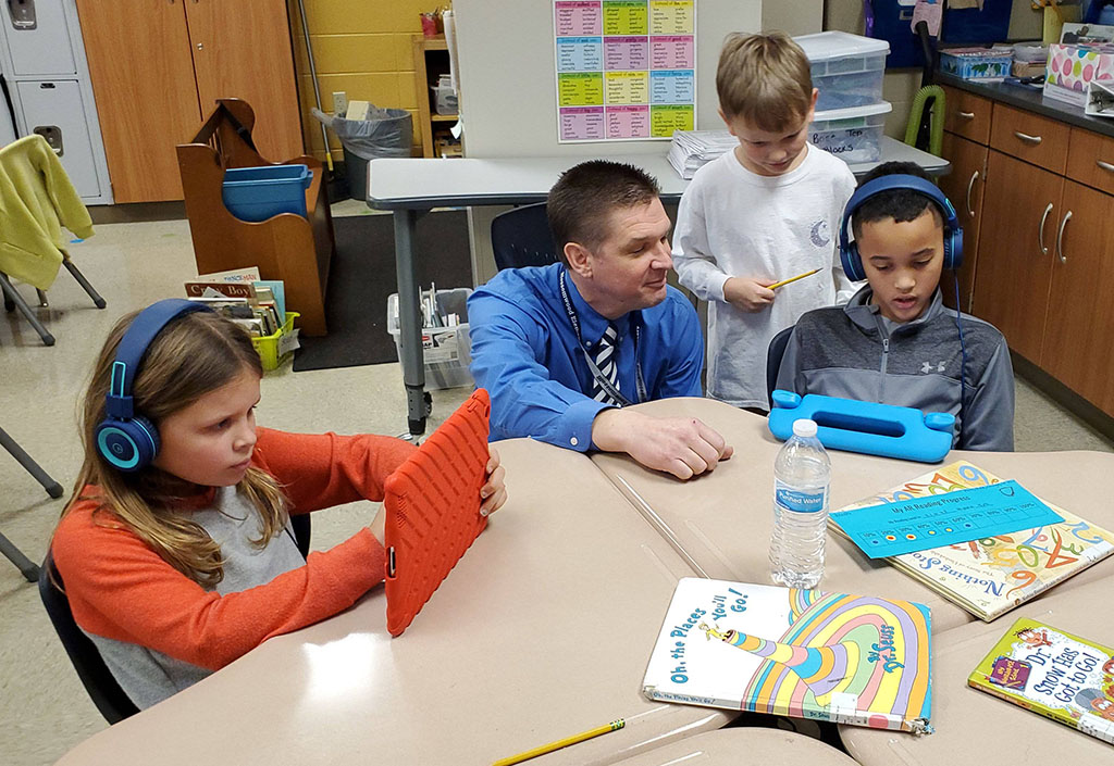Dr  Scott kneeling at a table helping students in the classroom