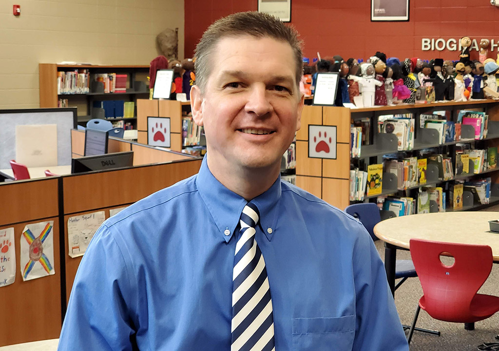 Dr Bradley Scott standing in the library at Blossomwood Elementary