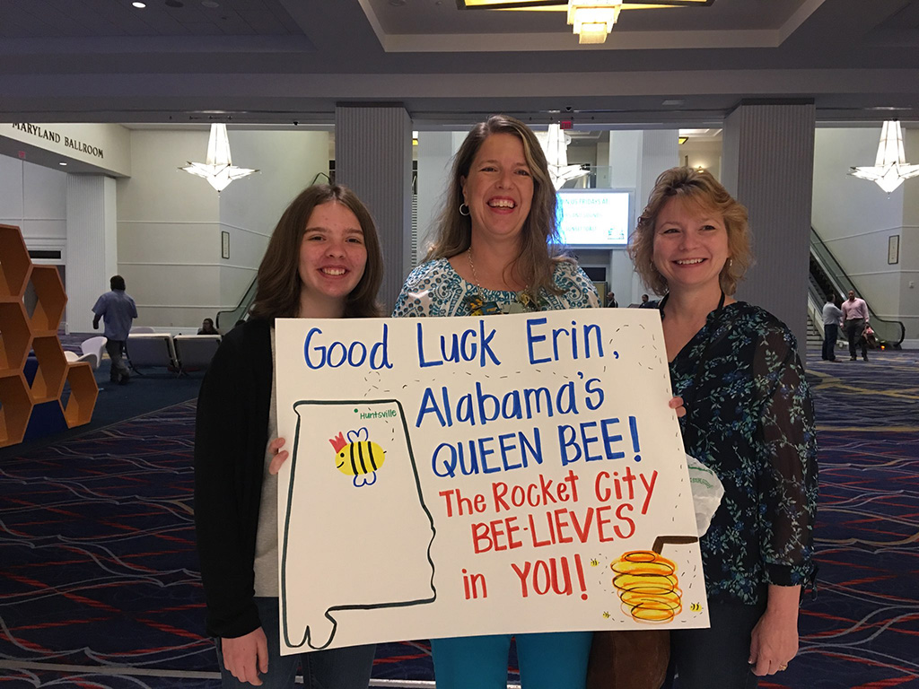 Erin Howard and Mr. Gap's Laura Pickens, school counselor and spelling bee coordinator, and teacher Tina Totora holding a sign whishing Erin good luck