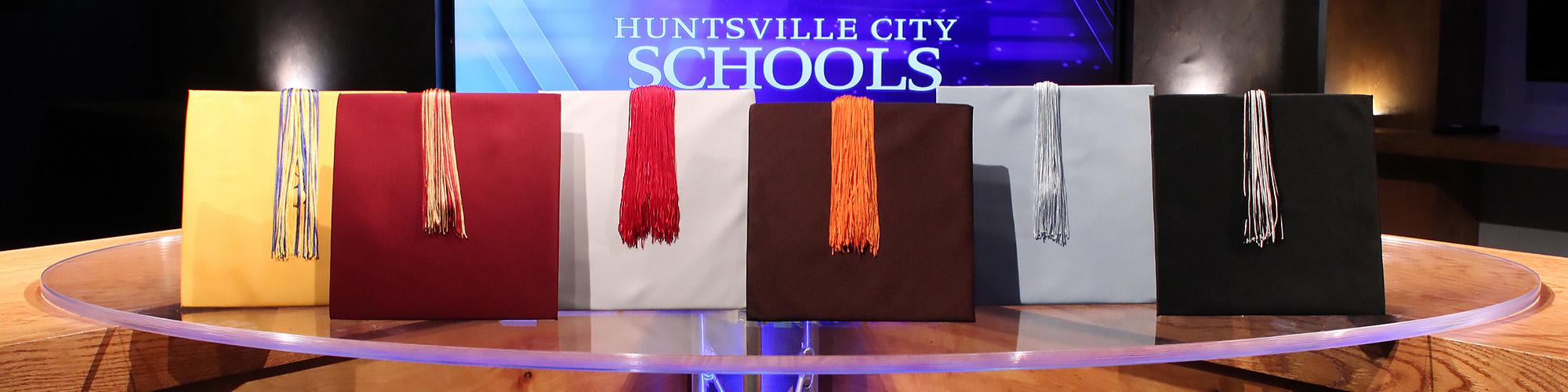 Graduation Caps from each high school lined up on a glass table in front of a screen with the text Huntsville City Schools