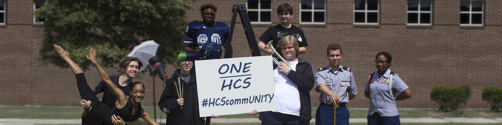 Lee and New Century dance, football, band, art, and JROTC students holding a sign which reads ONE HCS, #HCScommUNITY