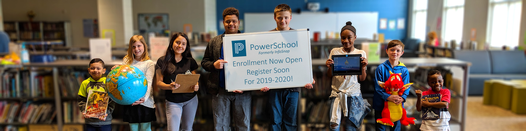 Students holding various school paraphernalia, including a sign that reads PowerSchool, Formerly InfoSnap, Enrollment Now open. Register soon for 2019-2020!