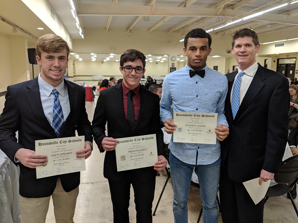 Trevor Ramos, Zack Strange, and Shannon Madry receiving awards from Scott Stapler for being a Scholar Athlete while at the 2019 Football Banquet