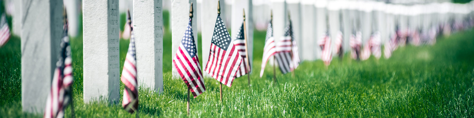 Memorial Day Banner - Series of military grave markers with american flags in the ground before them.