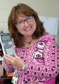 Mrs. Ann Clark smiling and holding a calculator