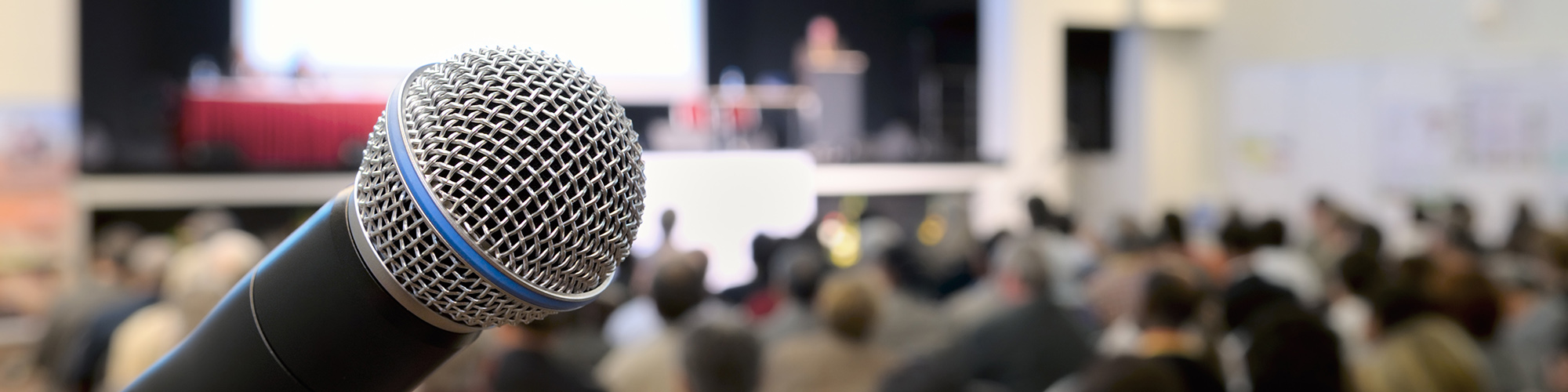 Microphone set in front of a blurred audience and presenter inside an auditorium