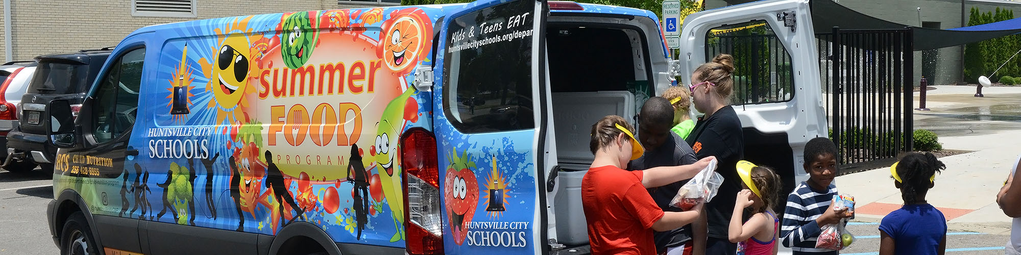 Children and a parent getting meals at the 2018 Summer Feed Program van