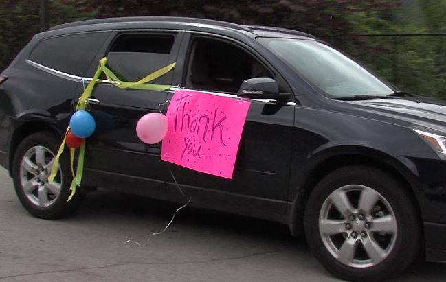 Car with a Thank You poster in the window driving by CNP volunteers