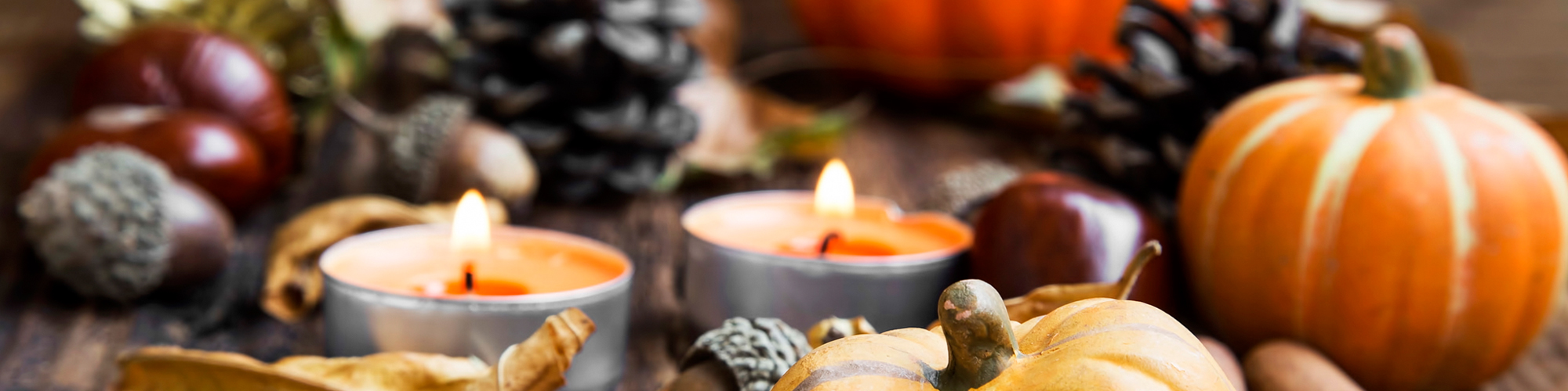 An assortment of Fall decorations, including pine cones, acorns, pumpkins, and orange candles