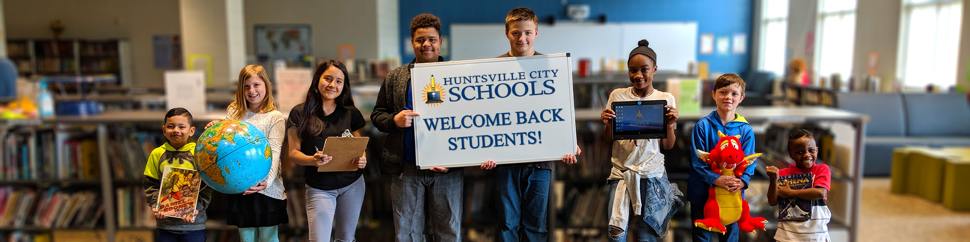"""Students in a library holding various objects and a sign that reads """"Welcome Back Students!"""""""