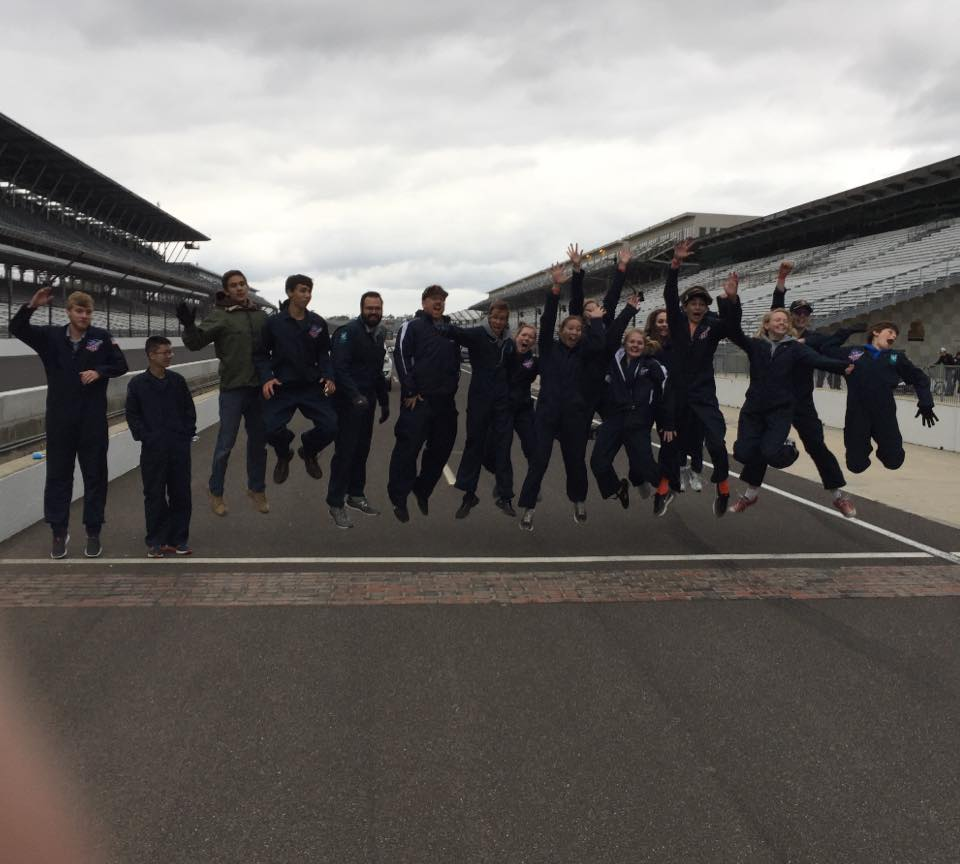 Students jumping in air over the bricks at the Indianapolis Motor Speedway after a Greenpower race.
