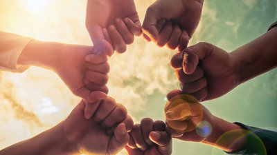 Hands of multiple races/ethnicities held in a solidarity circle