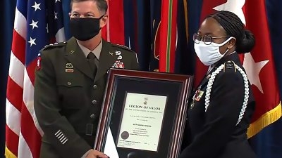 Ketty-Daphne Ngwese reciving the Bronze Cross award from Deputy Commander Lt. Gen. Flem B. Walker Jr