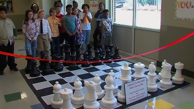 Giant chess set at MLK with chess club students standing behind it