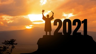 Silhouette of a young man in commencement robes on top of a mountain next to 2021