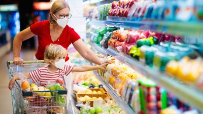 Mother and Daughter picking out fruit together at a grocery store