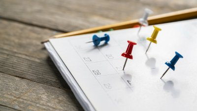 Calendar sitting on wood surface with multi-colored thumb pins on various dates, with a pencil in the background