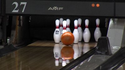 Bowling ball about to hit a set of bowling pins