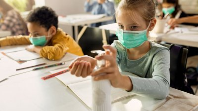 Young girl wearing a face mask and dispensing some hand sanitizer in a classroom