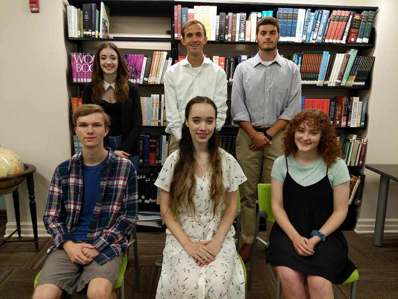 Six Huntsville High Seniors (three boys and three girls) standing and sitting in the library after being selected as 2020 National Merit Semifinalists