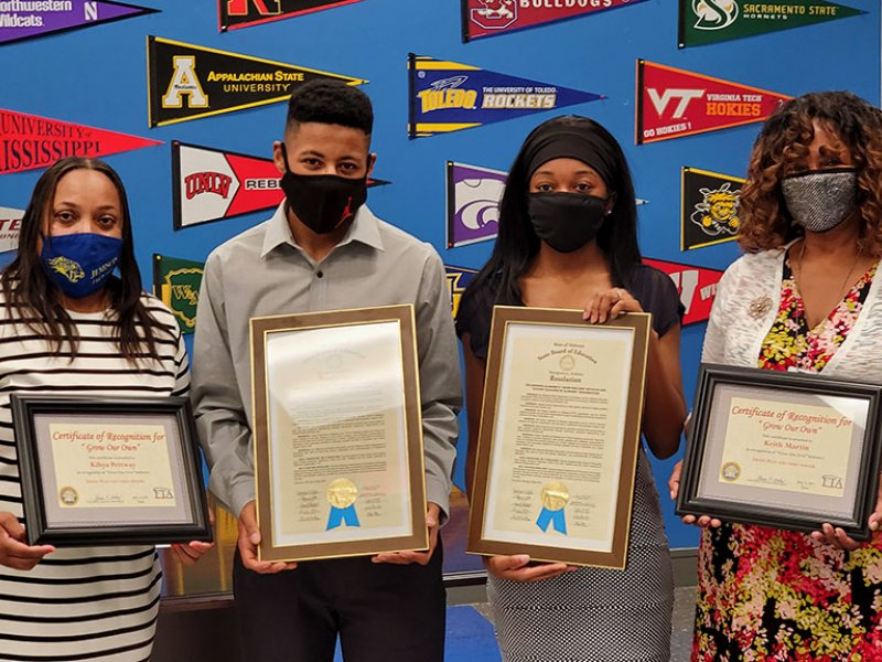 Keith Martin, Kihya Pettway, Dr. Leverette, and Ms. Johnson holding state board resolutions and Grow Our Own award plaques