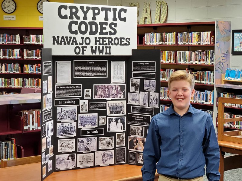 Colten Steele smiling in front of his project on the Navajo Code Talkers