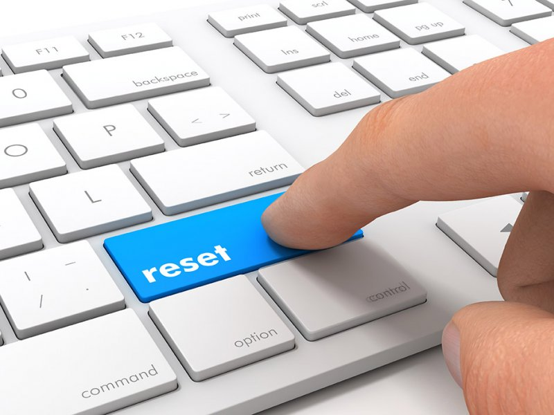 Finger pressing a blue Reset button on a white keyboard