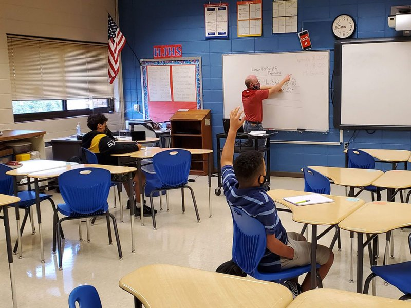 Socially-distanced student raising their hand while teacher explains a math problem