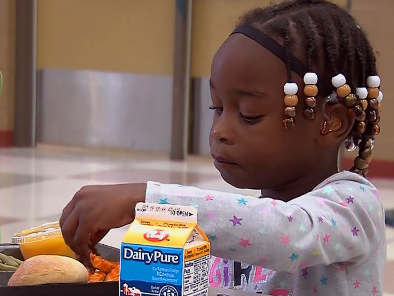 Young girl with beads in her hair eating a school lunch in the cafeteria