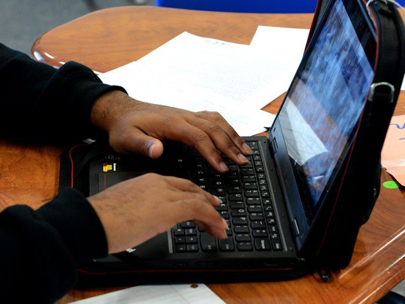 Students hands on laptop keyboard, completing a college application