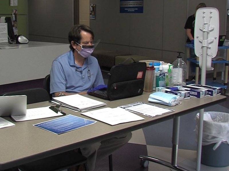 Principal Paul Bonner running a teacher check-in station during the COVID-19 Pandemic