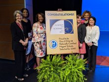 AAA Administration and HCS Staff next to Magnet Certification Poster