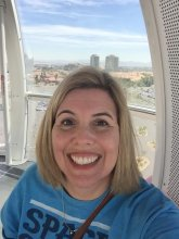 Mrs Amy Bergeson smiling in front of a window with a view of the city
