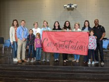 School & District Staff along with students holding up a congratulations banner at Blossomwood Elementary