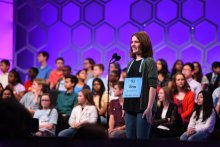 Erin conversing with the judges while at the mic at the 2019 Scripps Spelling Bee
