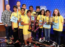 Erin and Octochamps posing with Jimmy Kimmel and other show members while holding their pieces of a broken trophy