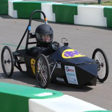 Female student driving a F24 Greenpower car at a race