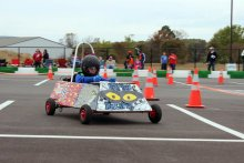 Student driving a Greenpower Goblin car for a race