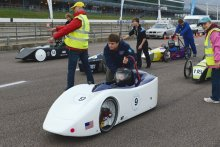 Students getting ready to start a Greenpower race by push-starting the cars
