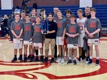 Hampton Cove 8th grade boys basketball holding championship trophy