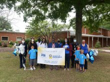 Highlands School staff and PTA personnel holding the PTA School of Excellence Banner