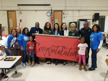 School & District Staff along with students holding up a congratulations banner at Highlands Elementary