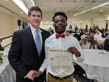 Jermyron Gilmore receiving award from Scott Stapler for Defensive Player of year at Football Banquet