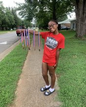Jerneisha Lewis holding her arm out, several track and field medals hanging from it