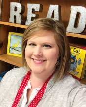 Ms. Kelli McLemore in front of a sign that says Read