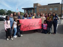 School & District Staff along with students holding up a congratulations banner at Morris Elementary