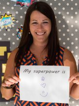 Ms. Melissa Turner holding a sign saying her Superpower is peace, love, and happiness
