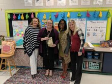 Amanda Harbin posing with principal and other district and school staff with her National Board Certification letter