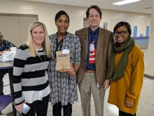 Chanel Leslie posing with principal and other district and school staff with her National Board Certification letter