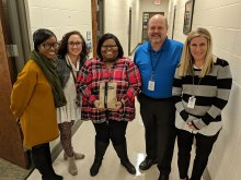 LaTorea Brooks posing with principal and other district and school staff with her National Board Certification letter